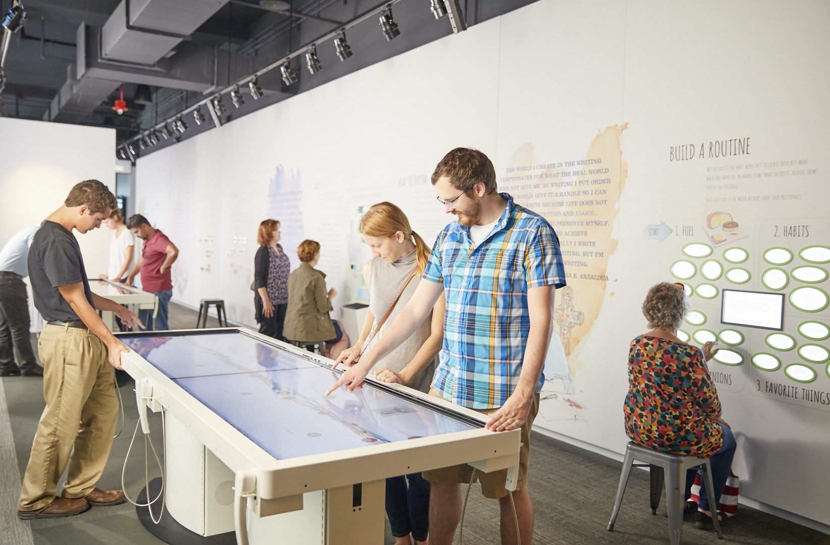 Visitors interacting with the Featured Works tables exhibit in the Mind of a Writer gallery