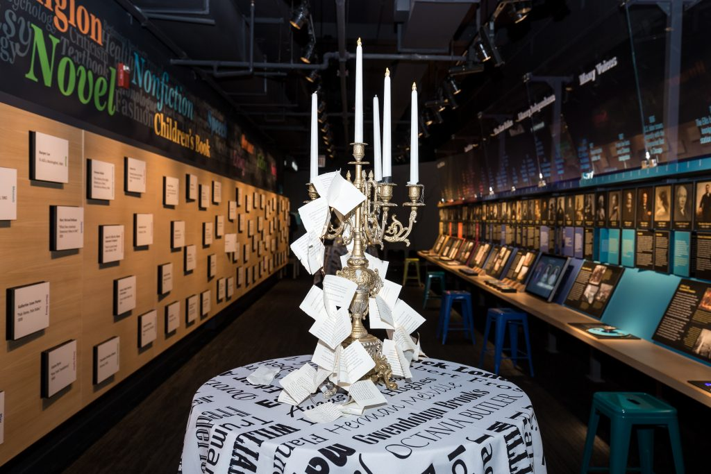 decorative candelabra draped with cut book pages on a table in the Nation of Writers gallery