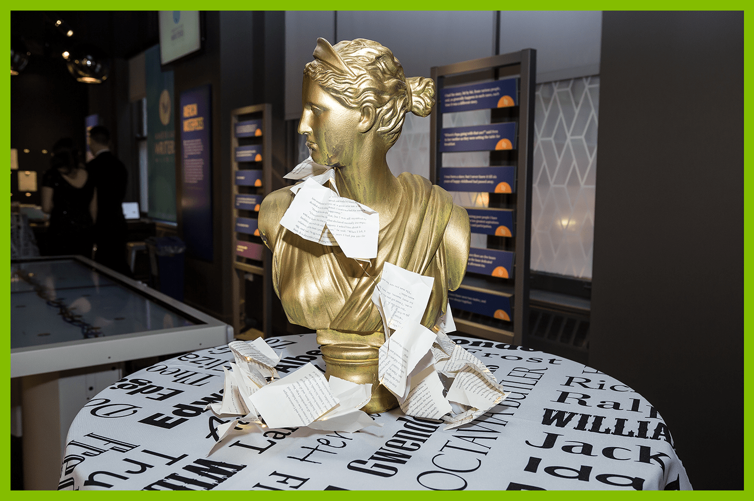 decorative gold bust draped with cut book pages sitting on a table in the Mind of a Writer gallery
