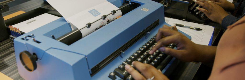 A visitor typing on a large blue IBM typewriter at the American Writers Museum
