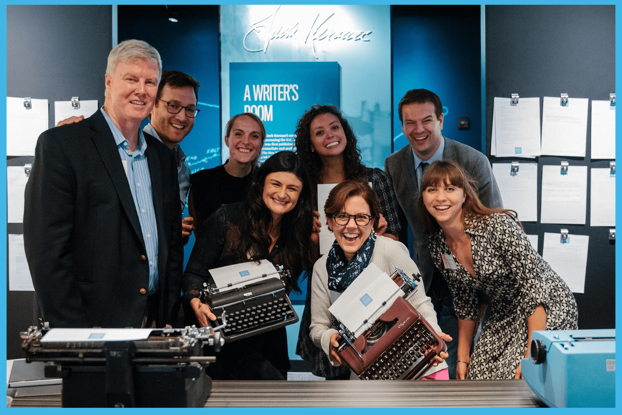 A group of eight people excitedly pose with typewriters at the Story of the Day exhibit
