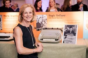 Christie Hefner posing with Hugh Hefner's typewriter