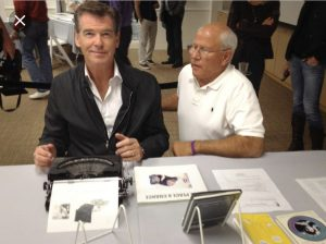 Pierce Brosnan types on John Lennon's typewriter, photo courtesy of Steve Soboroff